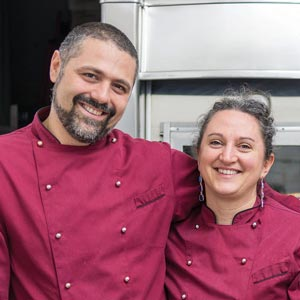 Two business owners posing for a picture in Chef jackets