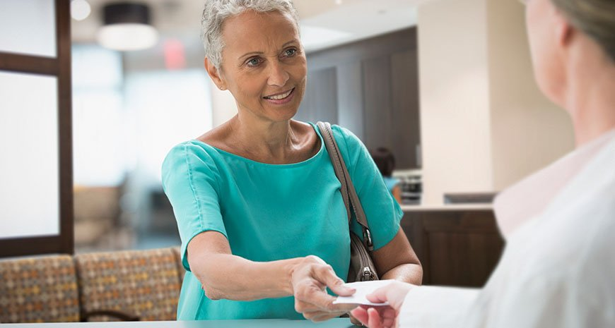 boomer woman handing over supplemental health insurance card