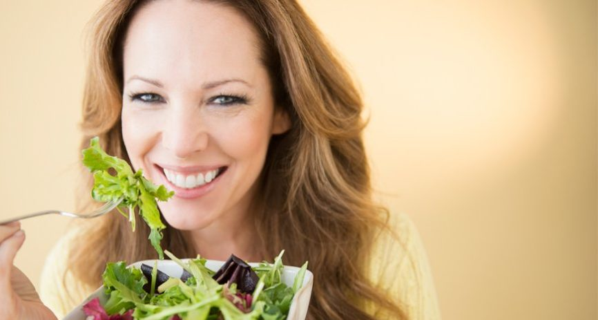 woman eating green salad with cancer fighting foods