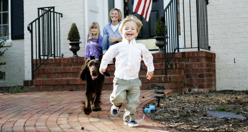 Little boy running in dress clothes ahead of his dog