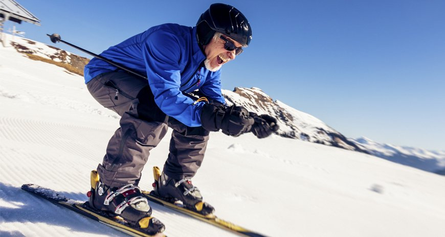 A man skiing down a hill for exercise.