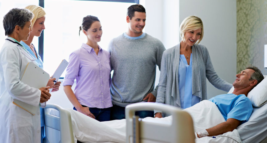 Patient with hospital indemnity insurance is laying in a hospital bed with family standing next to him.